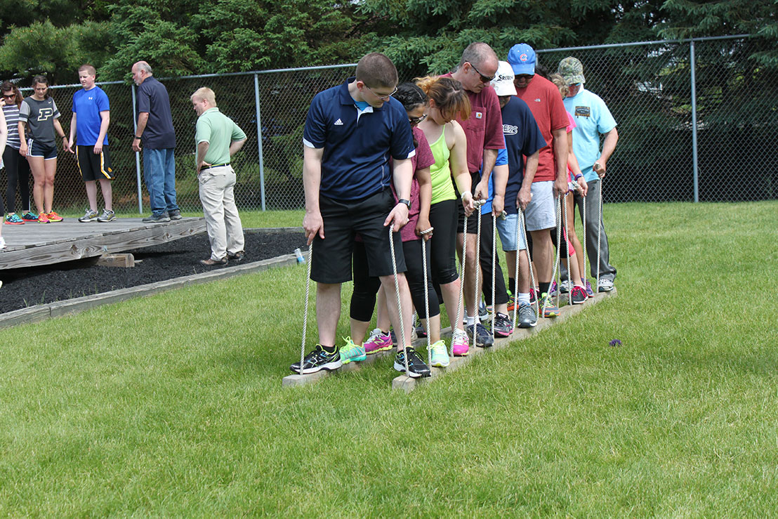 A group of adults participate in a team building exercise.