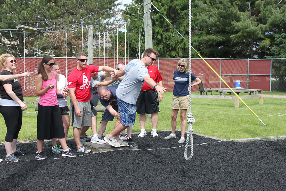 A local business group navigates a Beyond Boundaries Challenge Course obstacle.